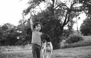 A small boy holds his ice cream away from his dog.