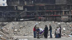 Syrian residents leave Aleppo's Bustan al-Qasr neighbourhood after pro-government forces captured the area in the eastern part of the war torn city on December 13, 2016. After weeks of heavy fighting, regime forces were poised to take full control of Aleppo, dealing the biggest blow to Syria's rebellion in more than five years of civil war.