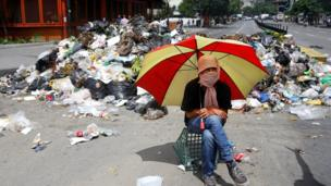 A demonstrator sits under an umbrella next to a pile of rubbish used as barricade in Caracas, Venezuela June 29, 2017