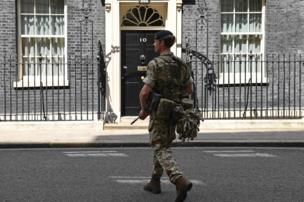 An armed member of the British Army carries his weapon as he patrols outside 10 Downing Street, the official residence of Britain's Prime Minister, in central London