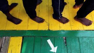 صورة لأقدام مهاجرين ينزلون من على متن سفينة
