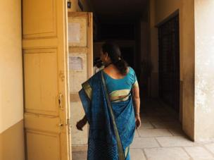 India, 2015. A woman in a sari walks along a passage.