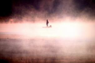 A man on his boat in the middle of mist