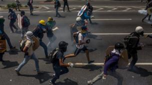 Caracas protesters run down the streets
