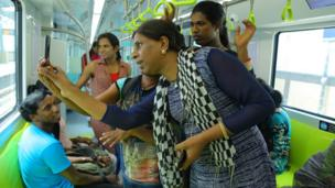 Transgender employees take selfies inside one of the new coaches of the Cochin metro
