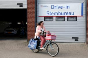 A cyclist casts a ballot in a drive-in polling station during the Dutch general election in Zuidplas, Netherlands, 15 March