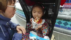 Toddler in a pram tucks into a hot dog as her mother watches, during the opening of the park.