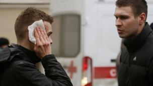 An injured commuter outside Sennaya Ploshchad metro station following explosions in St Petersburg, Russia, 3 April 2017