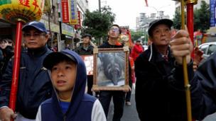 Một thành viên trong gia đình chủ nhân con heo thắng cuộc cầm ảnh của con heo này tại lễ diễu hành tại quận Sanxia, ở Tân Đài Bắc, Đài Loan, 0/02/2017.
