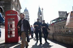 Armed police patrol a street near the Palace of Westminster, location of the Houses of Parliament, in central London.