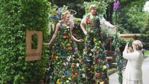 Stilt walkers dressed as hedges