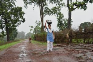 A girl carrying water back to her home.