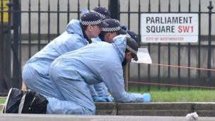 Police forensic officers in Parliament Square outside the Houses of Parliament in London