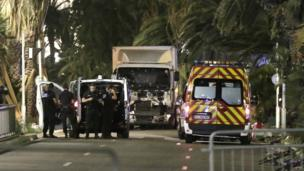 Lorry, riddled with bullet holes, with an ambulance, police van and police officers alongside, at the attack scene.