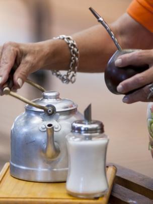 Mujer cebando mate con pava y azúcar.
