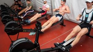 Competitors warm up on rowing machines on site ahead of their races