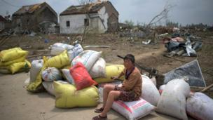 "A woman sits with her belongings in front of the rubble of her destroyed houses after a tornado in Funing, in Yancheng, in China""s Jiangsu province on June 24, 2016."