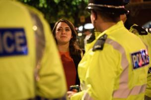 A tearful woman thanks police officers for all of their work following an evening vigil outside the Town Hall in Manchester, 23 May