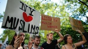 People hold up signs during a rally to support muslims rights as a counter protest to an anti-sharia law rally origanized by ACT for America on June 10, 2017 at Foley square in New York.