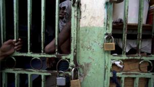 An ailing prisoner stands in a cell designated for sick prisoners near the infirmary in the National Penitentiary in downtown Port-au-Prince