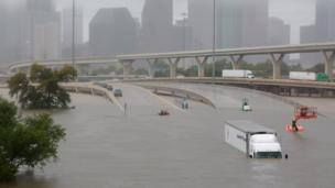 A flooded highway in Houston with a submerged lorry.