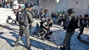 Israeli policemen detain a Palestinian protestor at Damascus Gate in the Jerusalem's Old City on December 8, 2017.