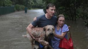 A man helps a neighbour down a street in Houston after rescuing her from her home in his boat in River Oaks, Houston (27 August 2017)