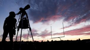 A woman looks through a telescope on a high school football field ahead of the eclipse.