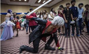 A man in a black and red cosplay outfit, carrying a plastic sword, crouches down on the floor in a pose in front of spectators at the event