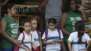 Workers of a school transport company wait with schoolchildren at the entrance of the Rocinha favela during a joint operation by the Police and Brazilian Armed Forces to fight heavily armed drug traffickers there, in Rio de Janeiro, Brazil, on September 22, 2017.