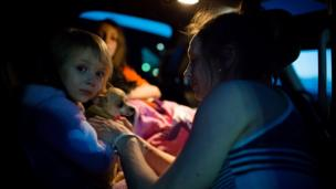 Fort McMurray resident Crystal Maltais buckles in her daughter, Mckennah Stapley, as they prepare to leave Conklin, Alberta