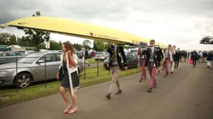 Rowers carry their boat during day two of the Henley Regatta.