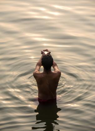 Un hombre tomando un baño ritual en el río Ganges durante el alba invernal