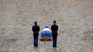 ઉચ્ચ અધિકારી અરનૌડ બેલટ્રેમના નિશ્વર દેહ પાસે ઊભેલા બે ફ્રેન્ચ રિપબ્લિકન ગાર્ડ