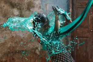 """فتاة تلهو أثناء إلقاء آخرين عليها مياها ملونة في عيد """"هولي"""" أو مهرجان الألوان، الذي يحتفي بقدوم فصل الربيع، وذلك في مدينة مومباي الهندية."""