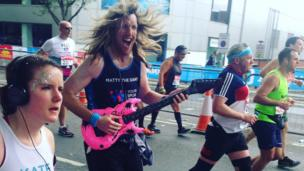 A marathon runner holds an inflatable pink electric guitar. He has long hair and a big smile.