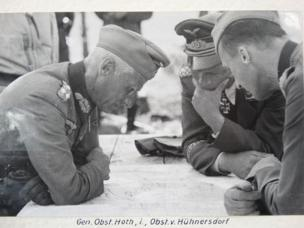 Generals Hoth, left, and von Hünersdorff right, lean intently over a map in full uniform, apparently deep in thought