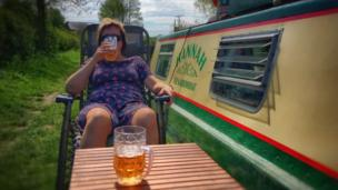 Two people having a beer by a towpath