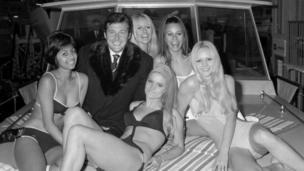 السير روجر مور وسط مجموعة من الفتيات
