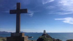 A cross above the coastal path towards Twr Mawr lighthouse at Ynys Llanddwyn, Anglesey
