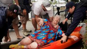 A resident is moved from a rescue boat onto a kayak in Dickenson, Texas (27 August 2017)