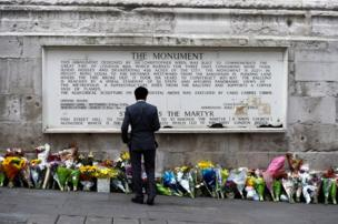 A man observes flowers left along the base of the Monument to the Great Fire of London