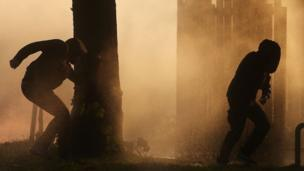 Two protesters outlined against the smoke during riots in Hamburg