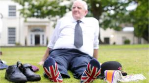 An Orangeman relaxes on grass with his shoes and uniform off, revealing union jack socks.