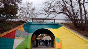 Youths walk through a tunnel decorated with a street art mural painting in Fanzara near Castellon de la Plana
