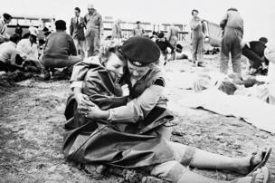 A volunteer embraces a woman wrapped in a blanket