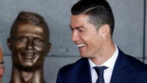 Cristiano Ronaldo stands in front of the statue of himself at Funchal airport,