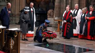 A member of the RAF laying a wreath on the tomb of the Unknown Soldier in Westminster Abbey.