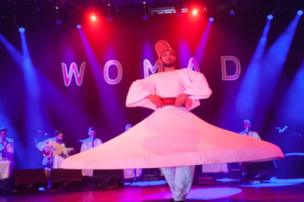 """A whirling dervish dances himself dizzy while Noureddine Khourchid, accompanied by six other Syrian singer-musicians, performs a series of sacred Sufi songs known as """"inshads""""."""