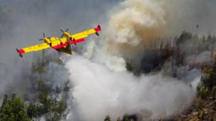 A Spanish Canadair firefighting aircraft drops water over the Pedrógão Grande forest fire, in central Portugal, 18 June 2017.